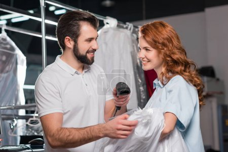 happy dry cleaning workers scanning barcode on bag with shirt