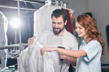 young dry cleaning workers scanning barcode on bag with shirt
