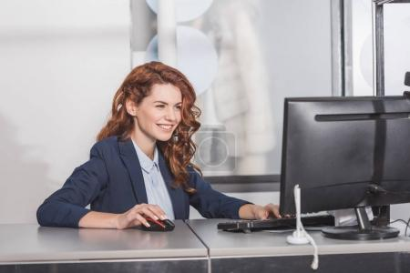 young happy manageress using computerat workplace