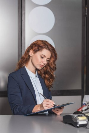 young beautiful manageress writing in clipboard at workplace with pos terminal