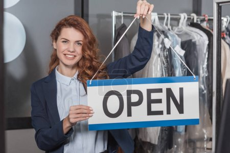 Photo pour Heureux jeune femme de ménage à sec tenant signe ouvert - image libre de droit