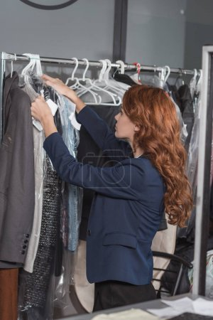 Photo for Dry cleaning manageress hanging clothes in bags at office - Royalty Free Image