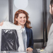 Dry cleaning manageress holding bag of clothes for...