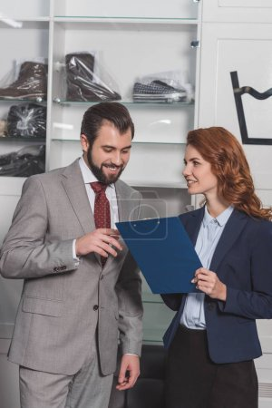 dry cleaning manageress writing order of handsome young man