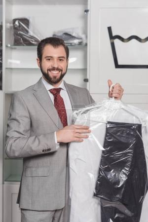 businessman holding plastic bag of clean clothing at dry cleaning