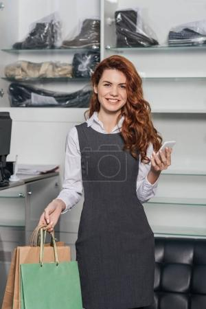 young woman with shopping bags and smartphone at dry cleaning