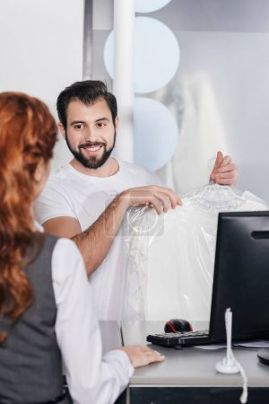 Photo for Smiling dry cleaning manager giving order to customer - Royalty Free Image