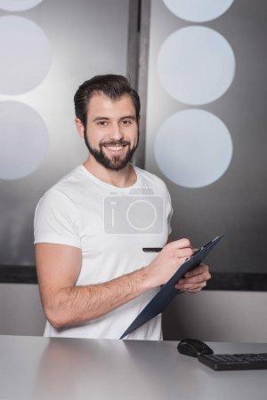 Photo pour Gestionnaire de jeune beau, assis au milieu de travail et d'écrire dans le presse-papiers - image libre de droit