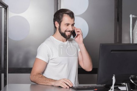 handsome young manager sitting at workplace and talking by phone