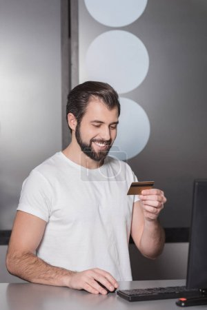 handsome young manager sitting at workplace with gold credit card