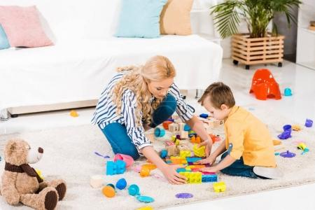 focused mother and little son playing with toys together on floor at home