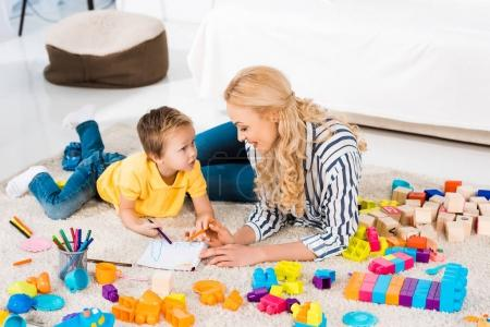 Photo for Young mother helping son while drawing picture together at home - Royalty Free Image