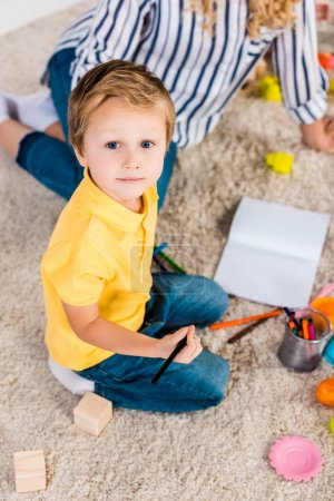 Photo for Selective focus of little boy looking at camera while drawing picture together with mother at home - Royalty Free Image