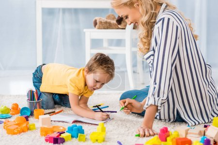 young mother helping son while drawing picture together at home