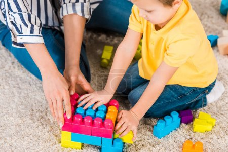 partial view of little boy and mother playing with toys at home