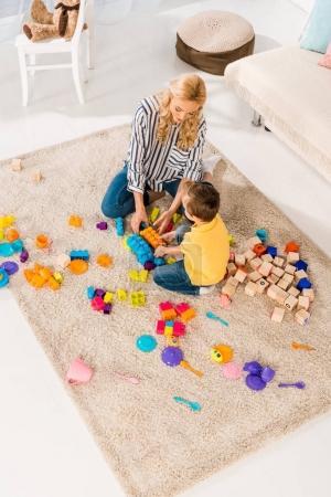 Foto de Vista de ángulo alto de la madre y el pequeño hijo jugando con juguetes juntos en el piso en casa - Imagen libre de derechos