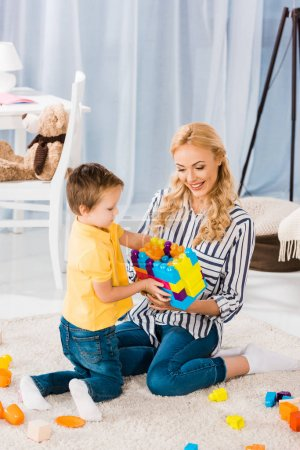 Foto de Madre e hijo jugando con juguetes juntos en el piso en casa - Imagen libre de derechos