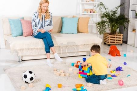 little boy playing with toys while mother using tablet on sofa at home