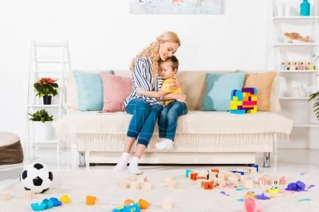 sensual mother and little son hugging each other while resting on sofa at home