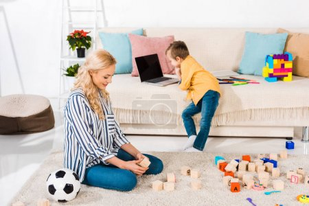 little boy using laptop on sofa while mother sitting on floor at home