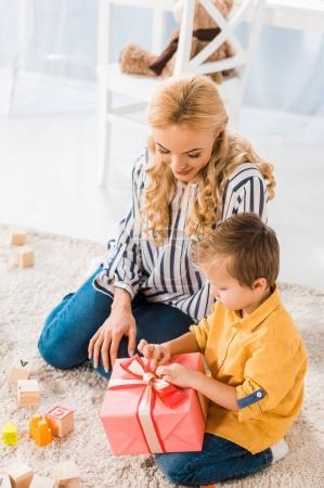 little boy opening wrapped gift from mother at home