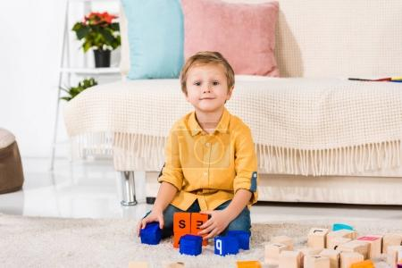 little boy looking at camera while playing with toys at home