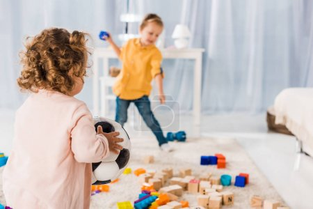 sibling playing with toys in living room