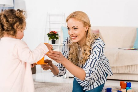 smiling mother giving daughter plastic toys