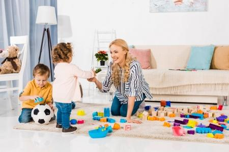 Photo for Happy mother and children playing with plastic blocks - Royalty Free Image