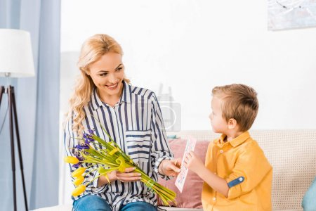 adorable son gifting mother bouquet and postcard on mothers day