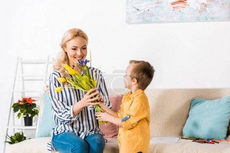 son gifting mother bouquet of flowers on mothers day