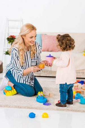 smiling mother and daughter playing with plastic cups