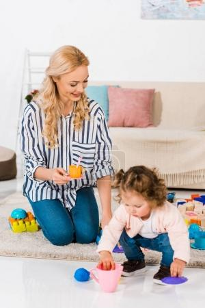happy mother and daughter playing with plastic cups