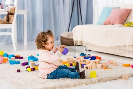 side view of adorable kid playing with plastic blocks on floor