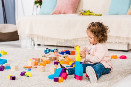 adorable kid playing with plastic blocks on floor