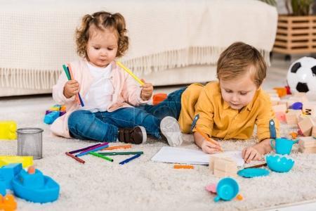 Photo pour Frères et sœurs adorables dessin sur un sol avec des crayons de couleur - image libre de droit