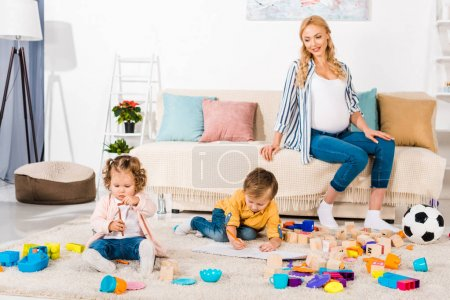 smiling pregnant woman looking how children playing on floor