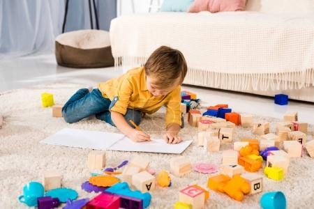 adorable kid lying on carpet and drawing with pencil