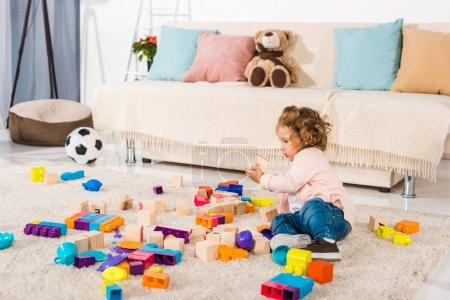 adorable child playing with wooden cubes and plastic blocks on floor