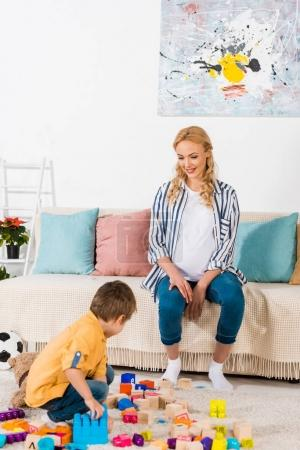 happy pregnant mother looking how son playing with toys