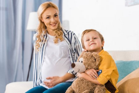 happy pregnant mother touching belly and son hugging teddy bear