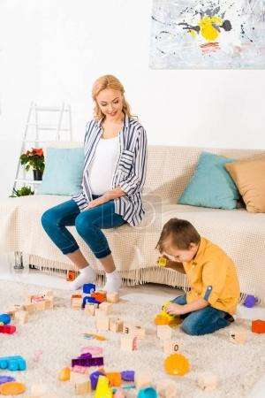 happy pregnant mother looking how son playing plastic blocks
