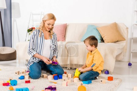 Photo for Pregnant mother playing plastic blocks with son - Royalty Free Image