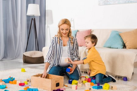 son showing wooden cube to smiling mother