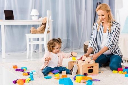Photo pour Heureux enceinte mère jouer avec petite fille - image libre de droit