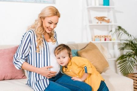 son listening pregnant mother belly