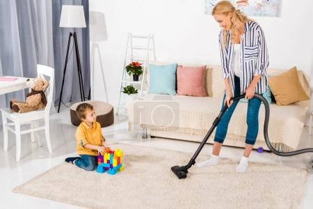 cute little boy playing with colorful blocks and looking at pregnant mother cleaning carpet with vacuum cleaner