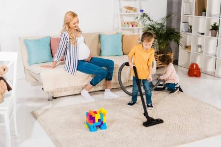 Photo for Happy pregnant woman looking at adorable little children cleaning room with vacuum cleaner at home - Royalty Free Image