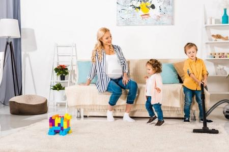 smiling pregnant woman looking at adorable little kids cleaning room with vacuum cleaner at home