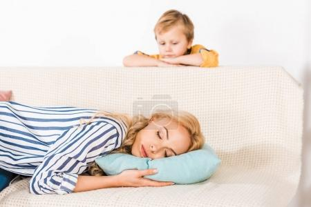 cute little boy looking at mother sleeping on sofa at home